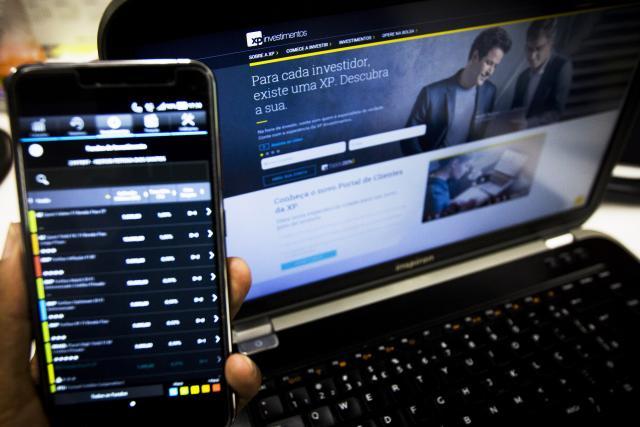 Desbancarização: Computador com a homepage da XP Investimento aberta e uma pessoa segurando o celular com a mesma página aberta na versão mobile