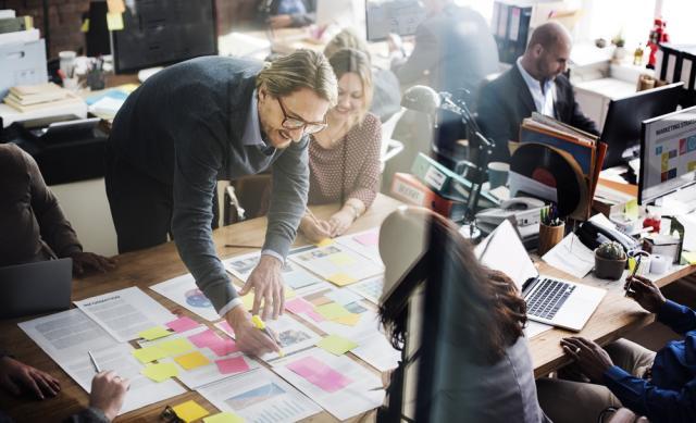 Grupo de pessoas discutem projeto em uma mesa de trabalho com papeis e post-its