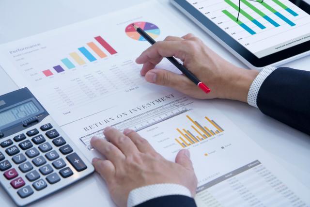 Mão masculina sobre papéis com desenhos conceituais de gráficos ao lado de uma calculadora
