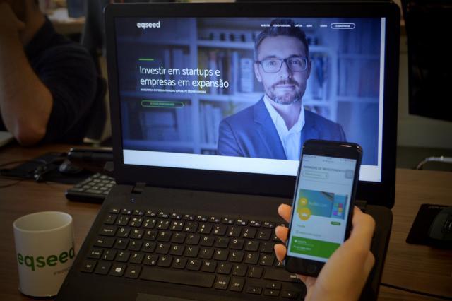 Desbancarização: Computador com a homepage da EqSeed aberta e uma pessoa segurando o celular com a mesma página aberta na versão mobile