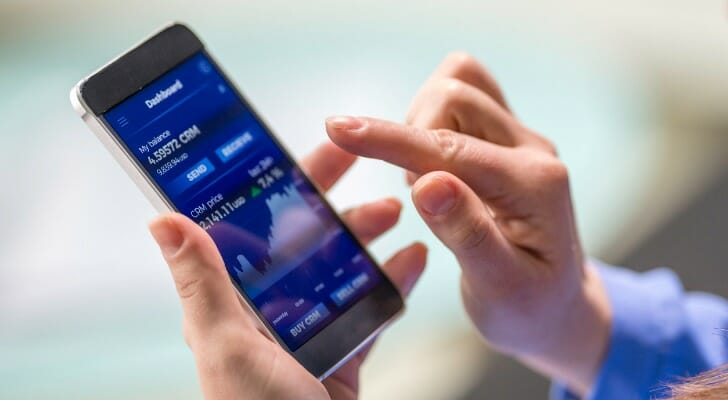 Desbancarização: Mulher com o dedo na tela simulando um investimento pelo celular