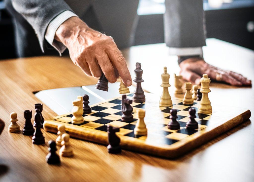 qual investimento rende mais: mão masculina mexe na peça de xadrez em tabuleiro