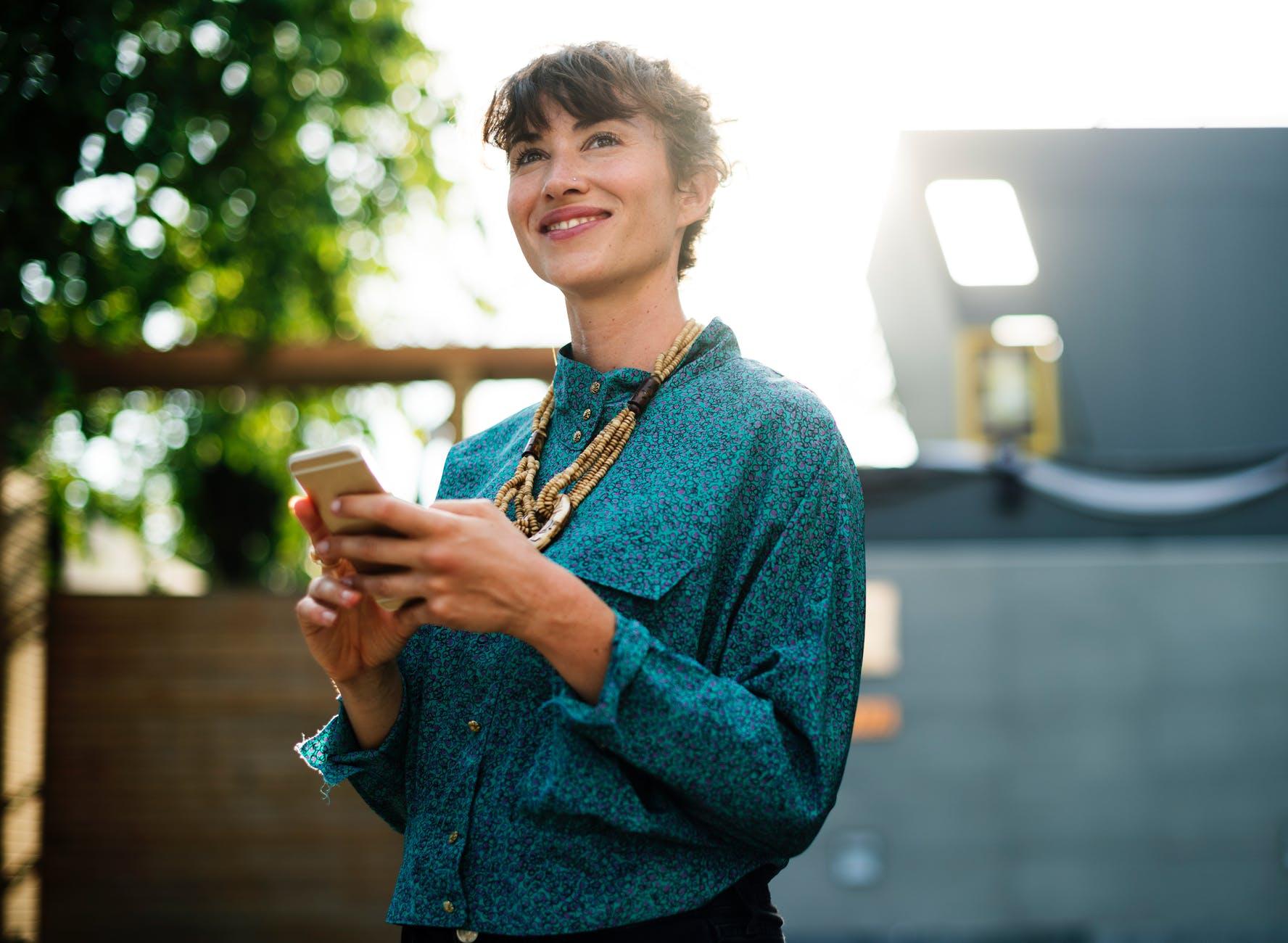 mulher com celular na mão simulando um investimento