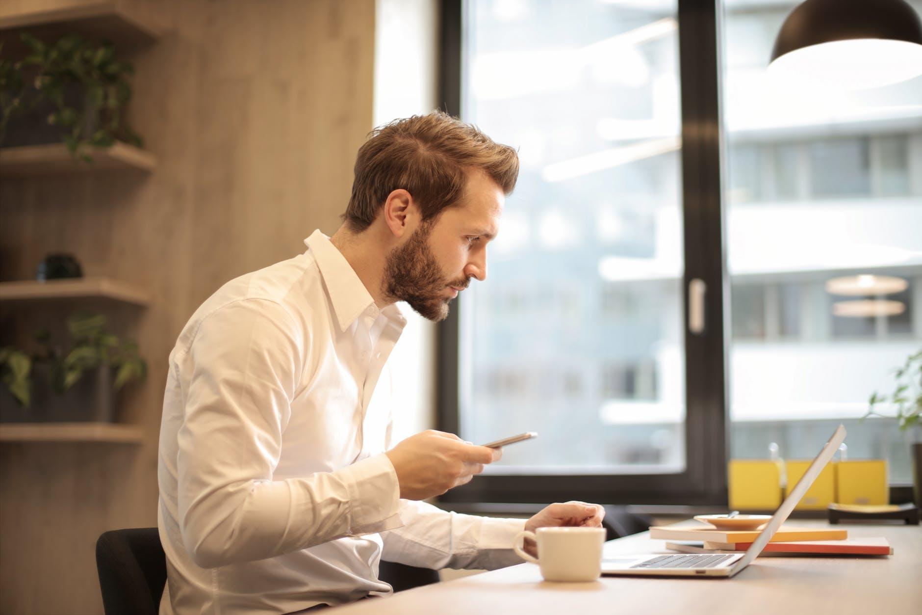 qual investimento rende mais: homem confere o notebook e o celular, simulando um investimento