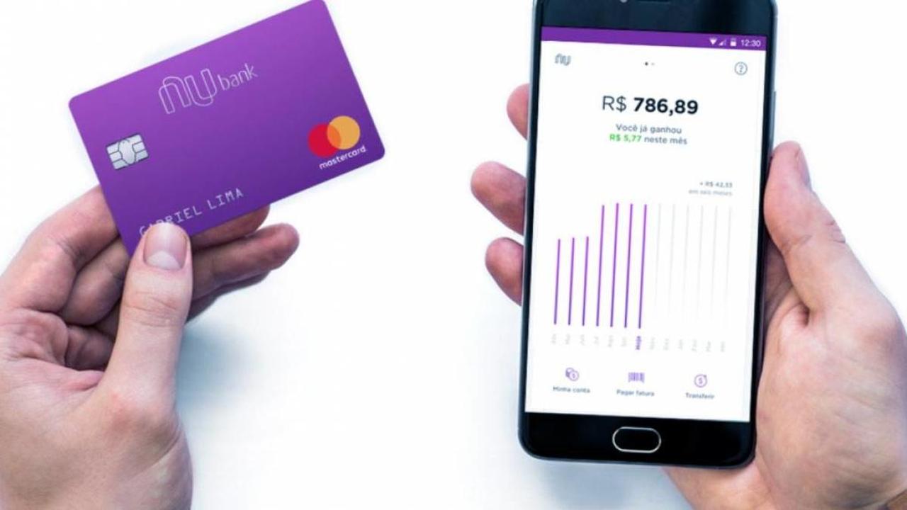 Empresa startup brasileira: cartão do banco Nubank seguro na mão esquerda e o app do celular aberto na mão direita