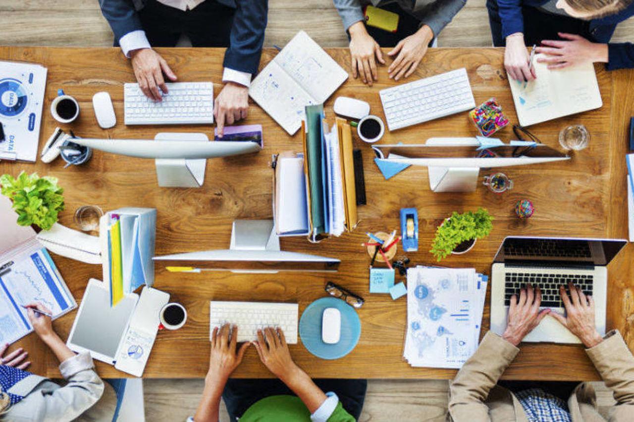 Startup: foto de cima de uma mesa com pessoas trabalhando em computadores