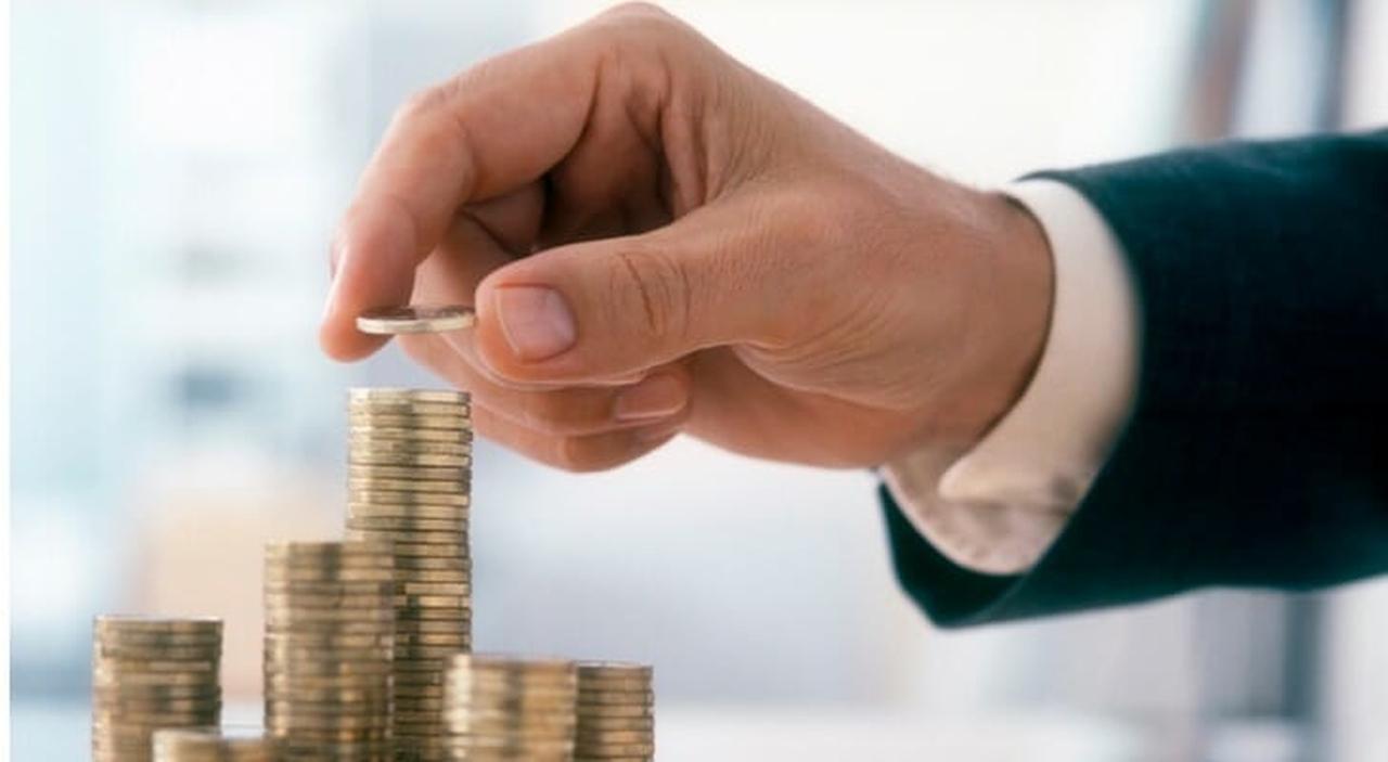Melhores investimentos a longo prazo: mãos masculina colocando uma moeda dourada em pilha de moedas sobre a mesa