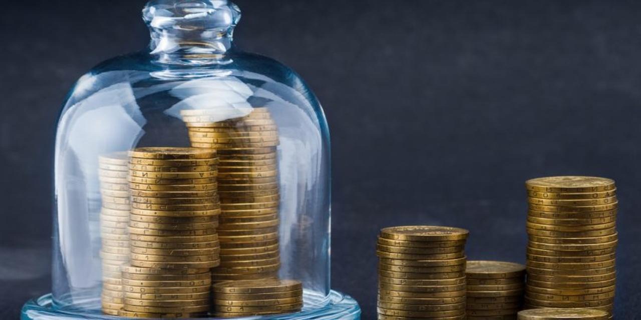 Melhores investimentos a longo prazo: moedas douradas empilhadas em uma mesa