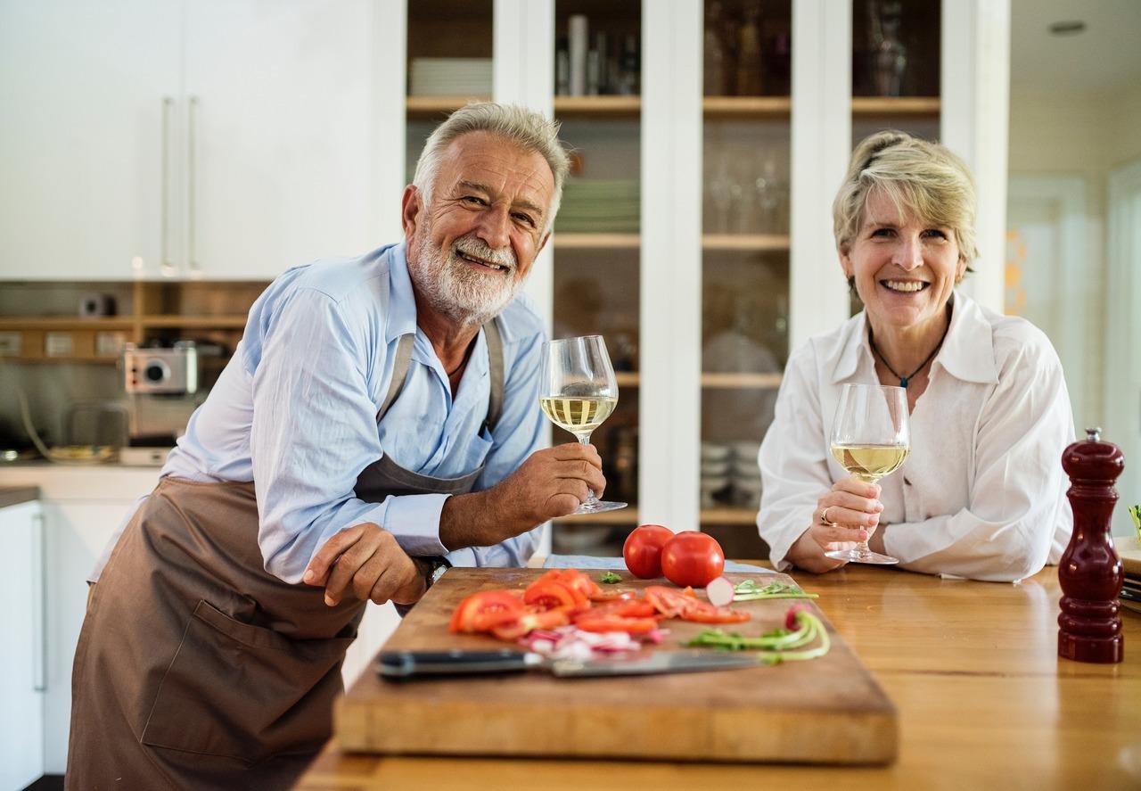 Investimentos para a aposentadoria: casal mais velho toma vinho branco e se apoa em bancada na cozinha com tira-gostos