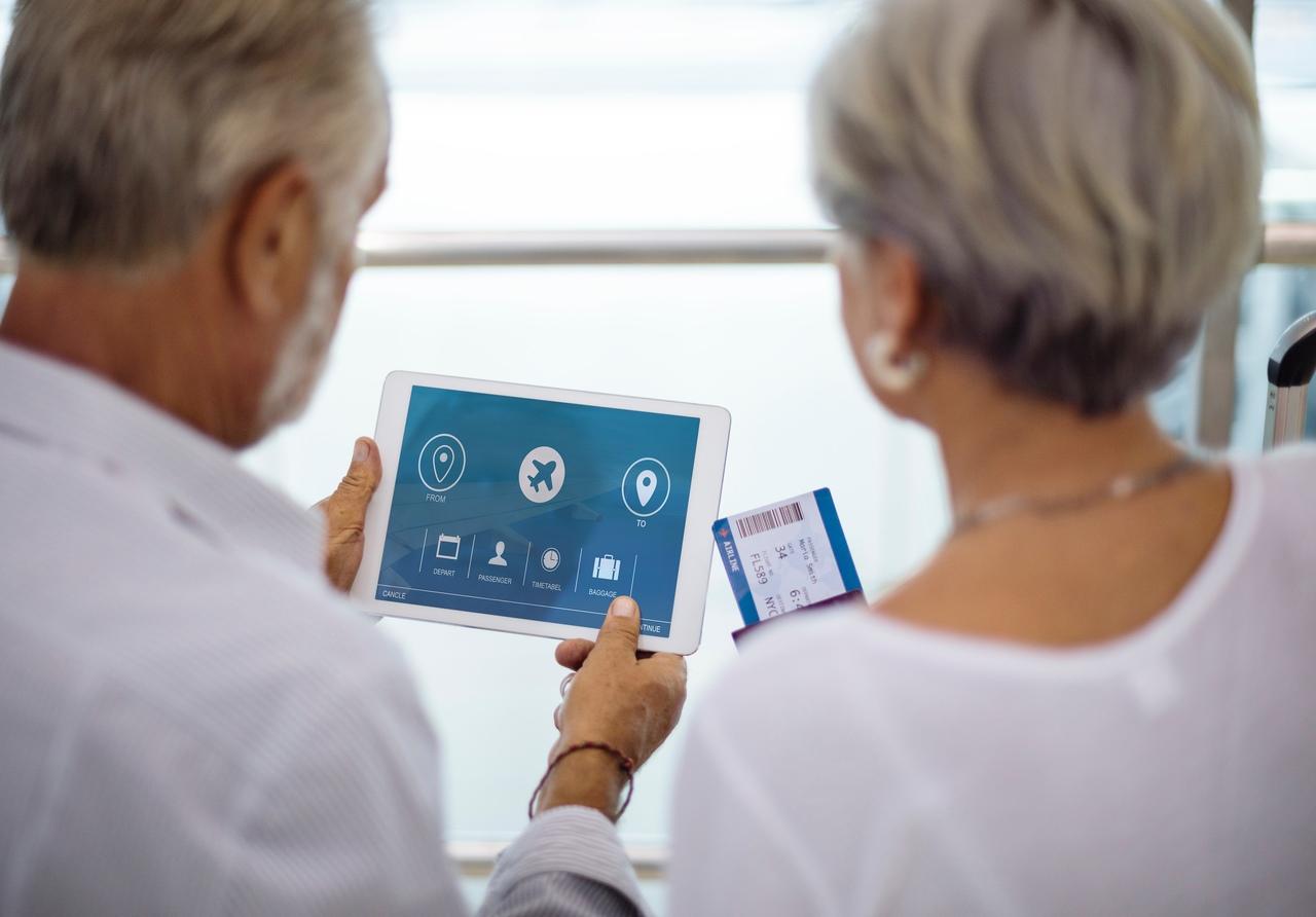 Investimentos para a aposentadoria: casal mais velho olha para um tablet