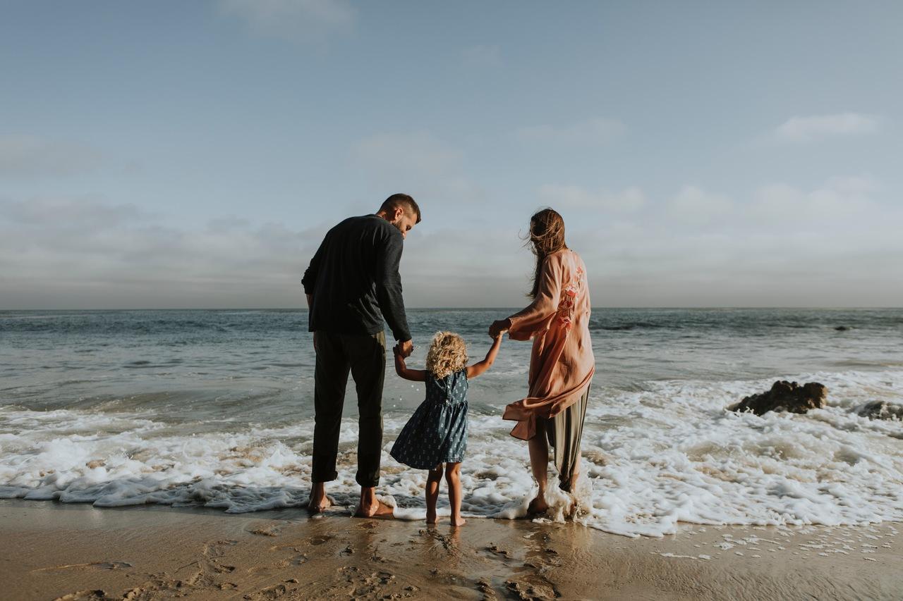 Investimentos para a aposentadoria: mãe e pai brincam com a filha na beira da praia