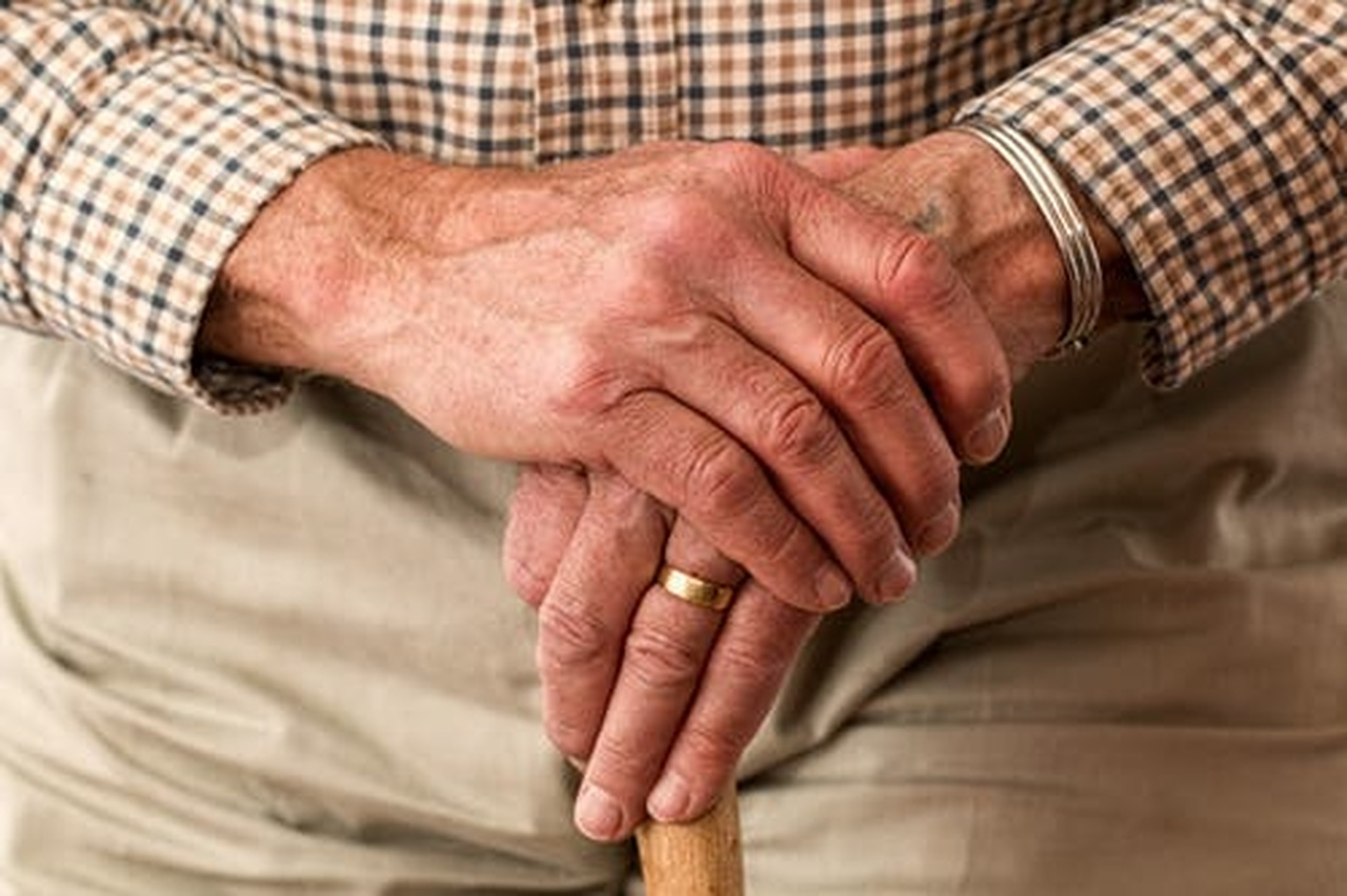 Investimentos para a aposentadoria: mão idosa segurando uma bengala