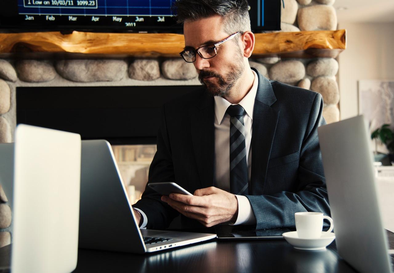 Como empreender sem sair do trabalho executivo com celular na mão esquerda na mesa