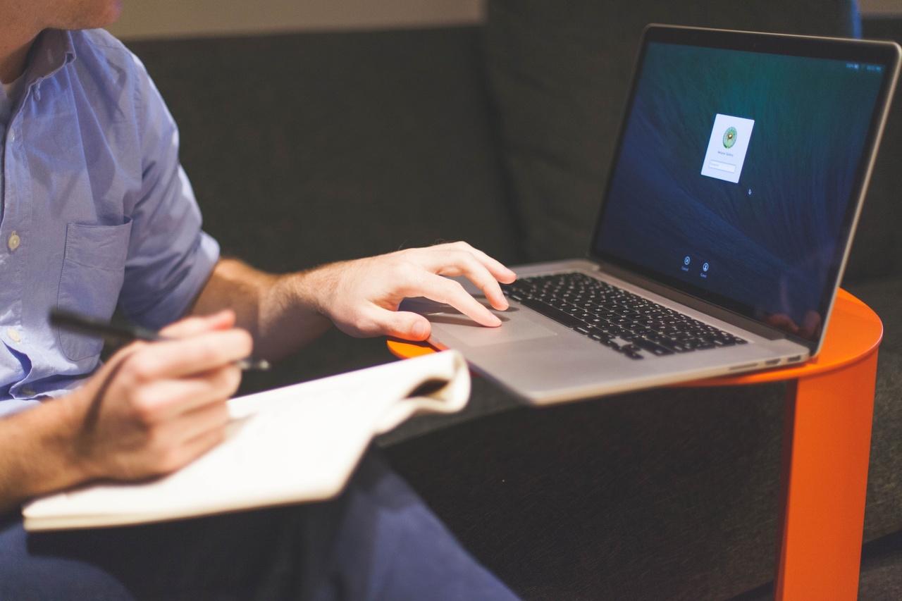 Como empreender sem sair do trabalho homem ao lado de notebook sentado no sofá