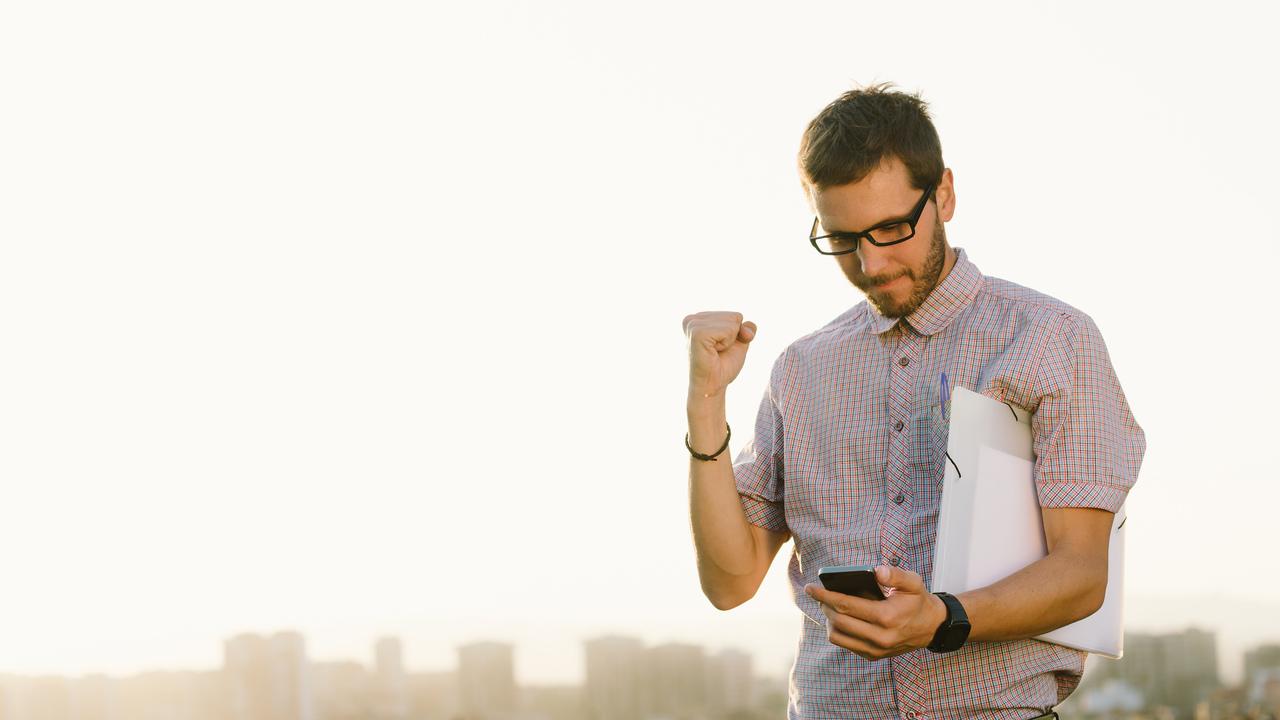 Como empreender sem sair do trabalho homem vestido com roupa social olha para o celular e comemora com punho cerrado
