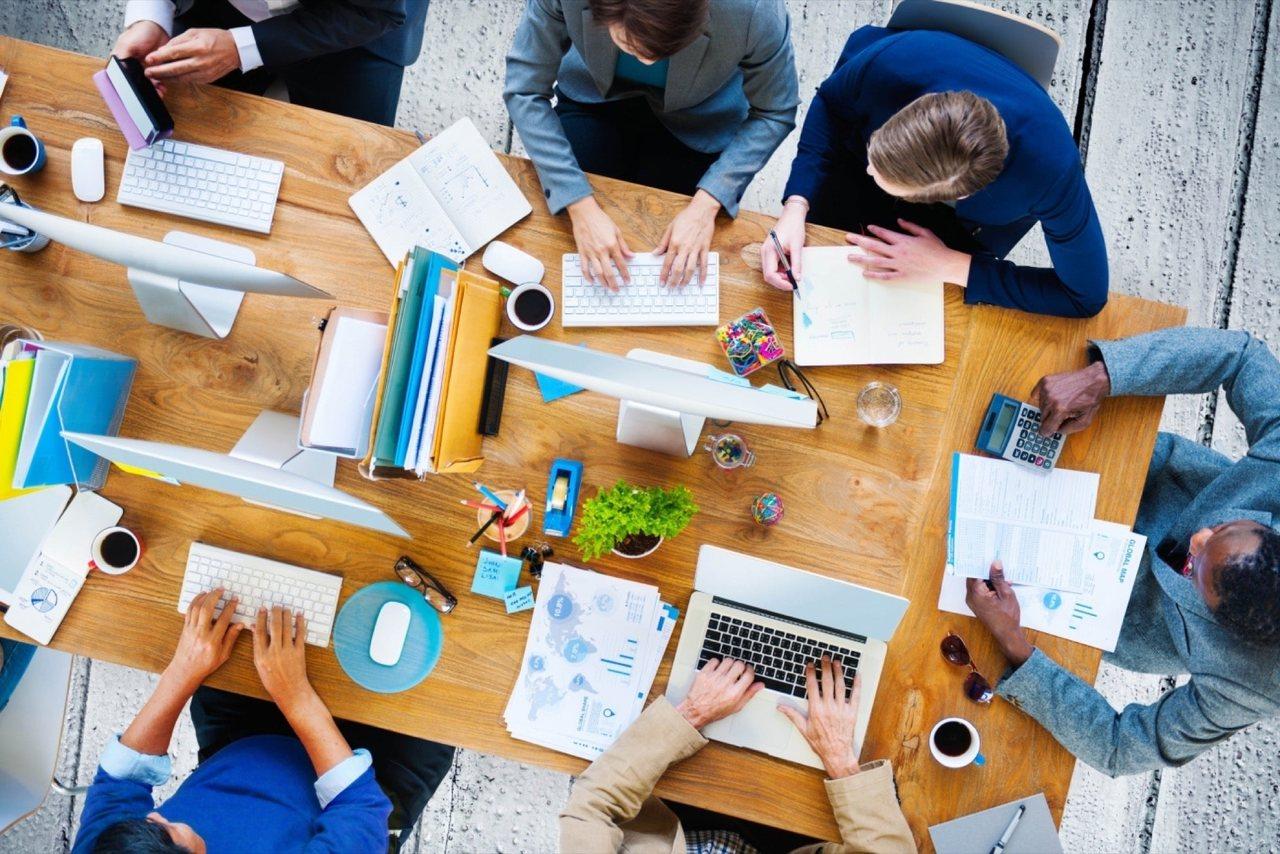 scale-up: vista de cima de uma mesa de trabalho com homens e mulheres sentadas