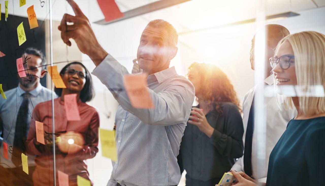 scale-up: trabalhadores colam post-it em um virdro e sorriem animados