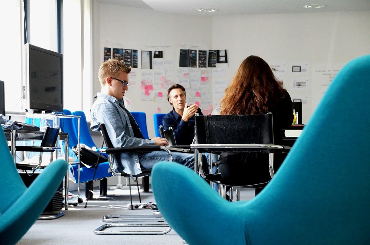 scale-up: três pessoas conversam em uma reunião sentadas próxima a uma mesa e cadeiras vazias