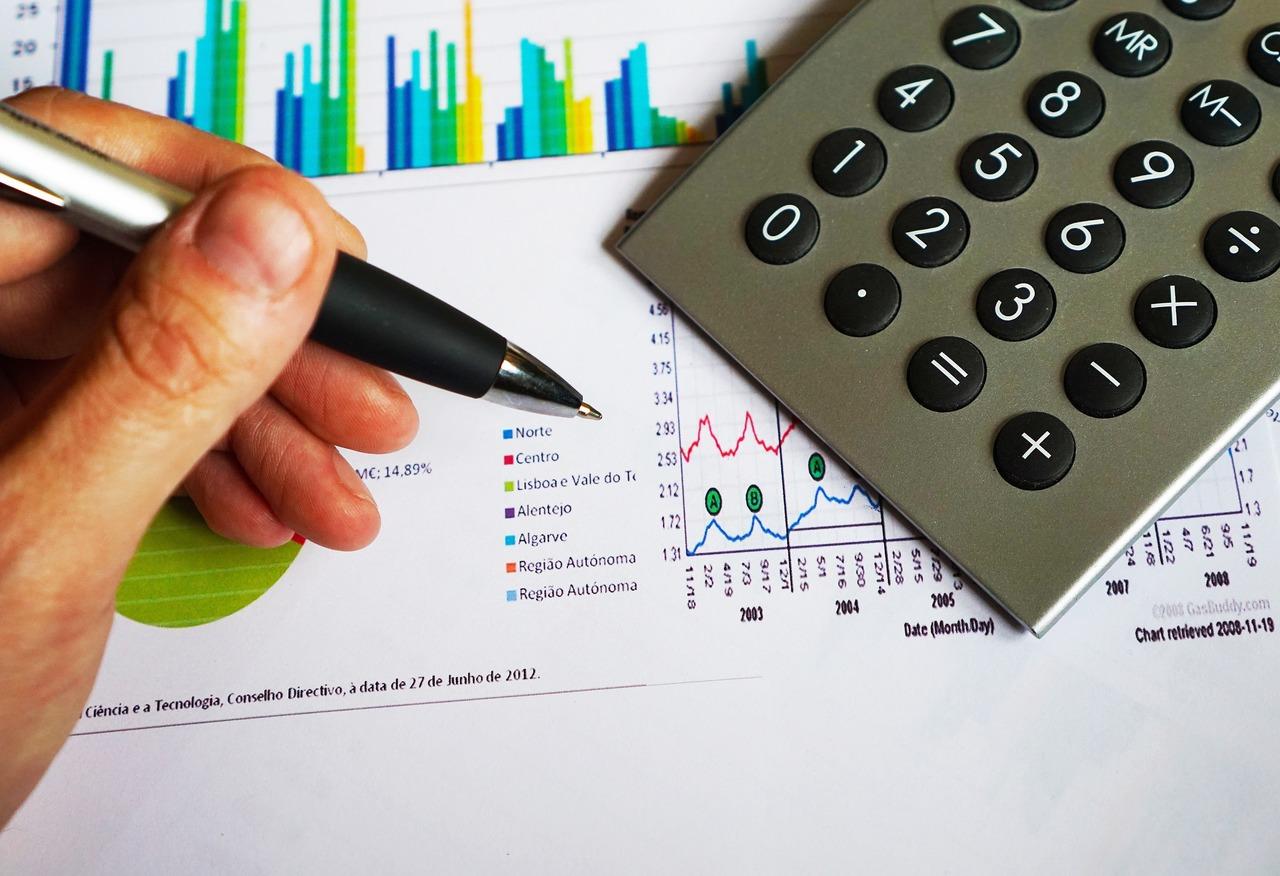 Capital de Risco - Pessoa com caneta na mão ao lado de uma folha com gráficos e uma calculadora