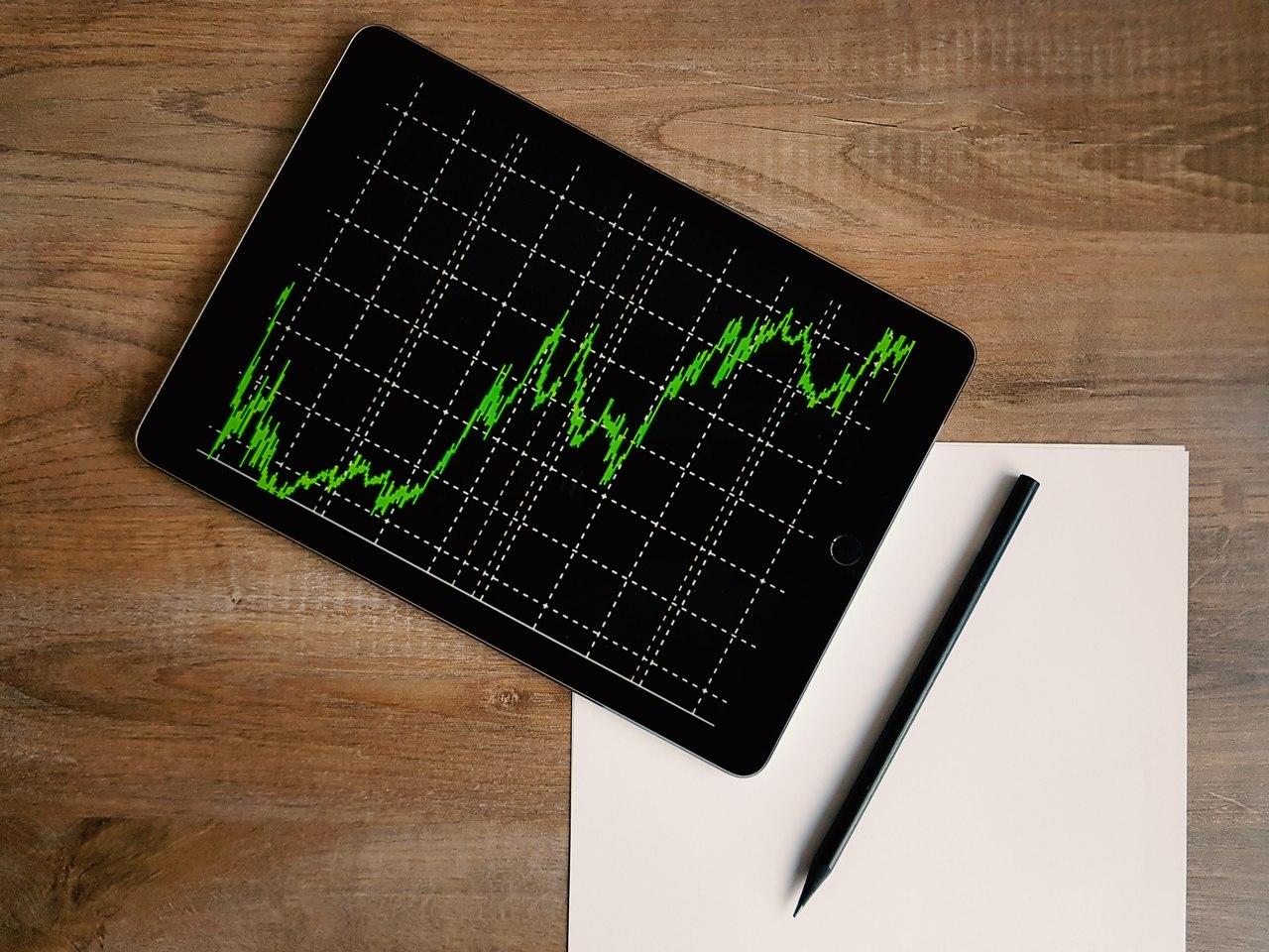 Renda Variável - tablet com gráfico de crescimento apoiado em uma mesa ao lado de um lápis e um papel