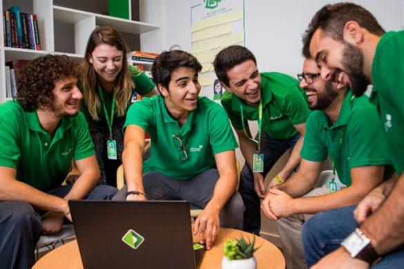 Jovens funcionários da Stone sorriem um para o outro em frente ao computador