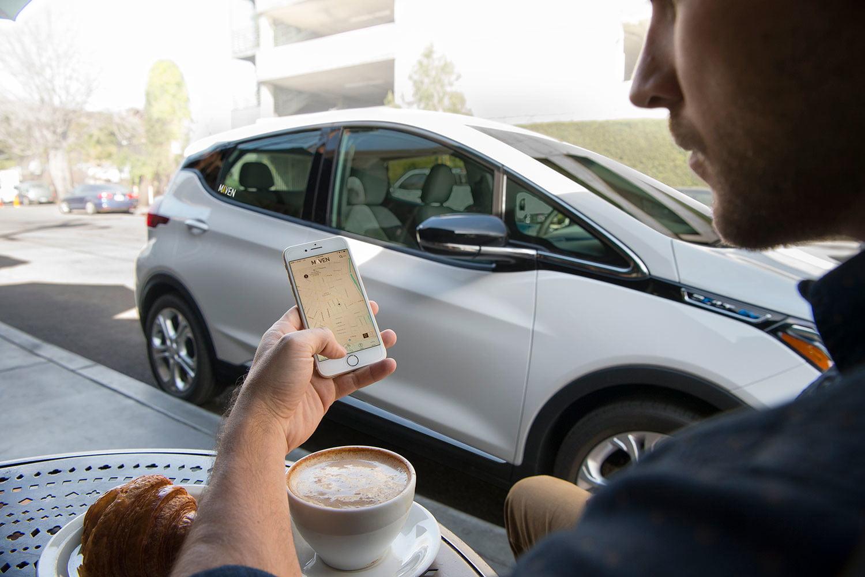homem com celular na mão em frente ao carro