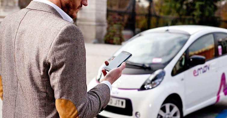 carsharing: homem olha para o ceular em frente à um carro elétrico
