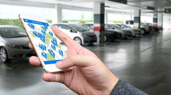 carsharing: mão segura um celular em uma garagem de prédio