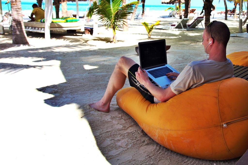 startups e lifestyle business: homem usa notebook sentando na praia
