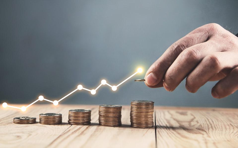 O que é IPO: mão masculina segura moeda sobre uma pilha de moedas em mesa