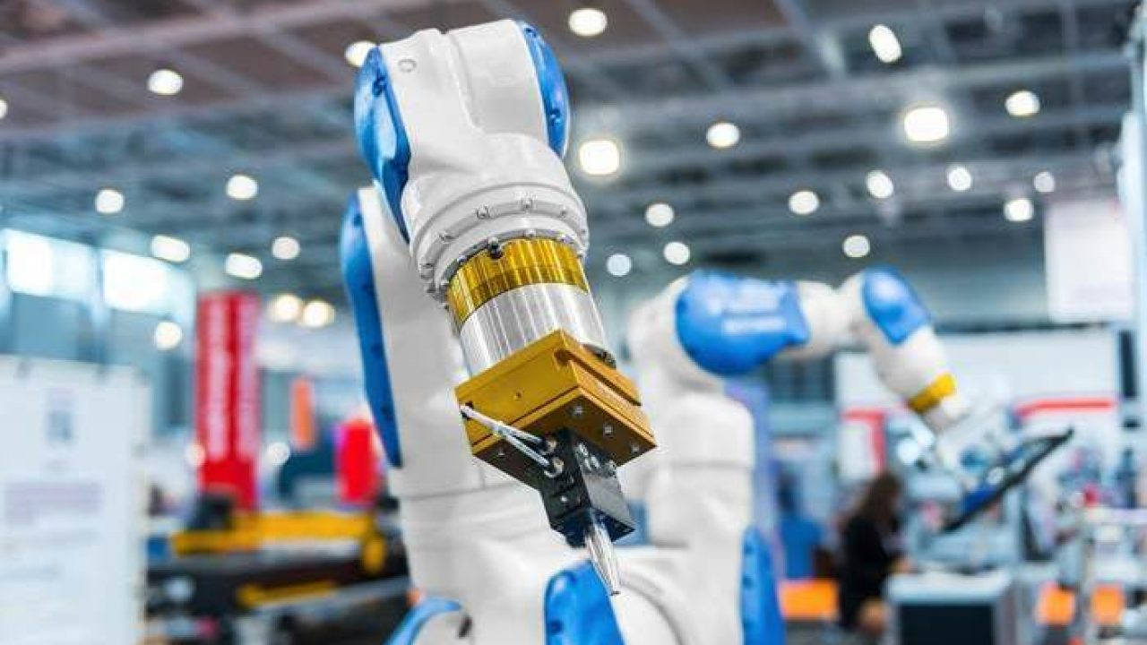 setor para investir indústria 4.0: robô em fábrica futurística com fundo borrado